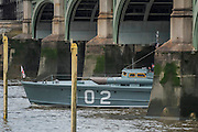 A restored WW2 motor torpedo boat emerges from Westminster Bridge and passes the Houses of Parliament as par of the flottilla on the River Thames - Queens 90th birthday was celebrated by the traditional Trooping the Colour as well as a flotilla on the river Thames.