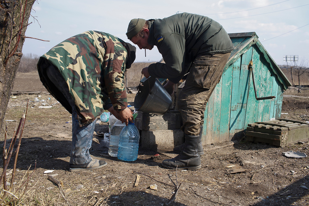 Volunteers with Dnipro-1 battalion collect water from a well at a damaged house near the bridge on March 20, 2015 near Pisky, Ukraine.