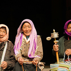 Three old women spinning their praying wheels in front of the local monastery in Tibet.