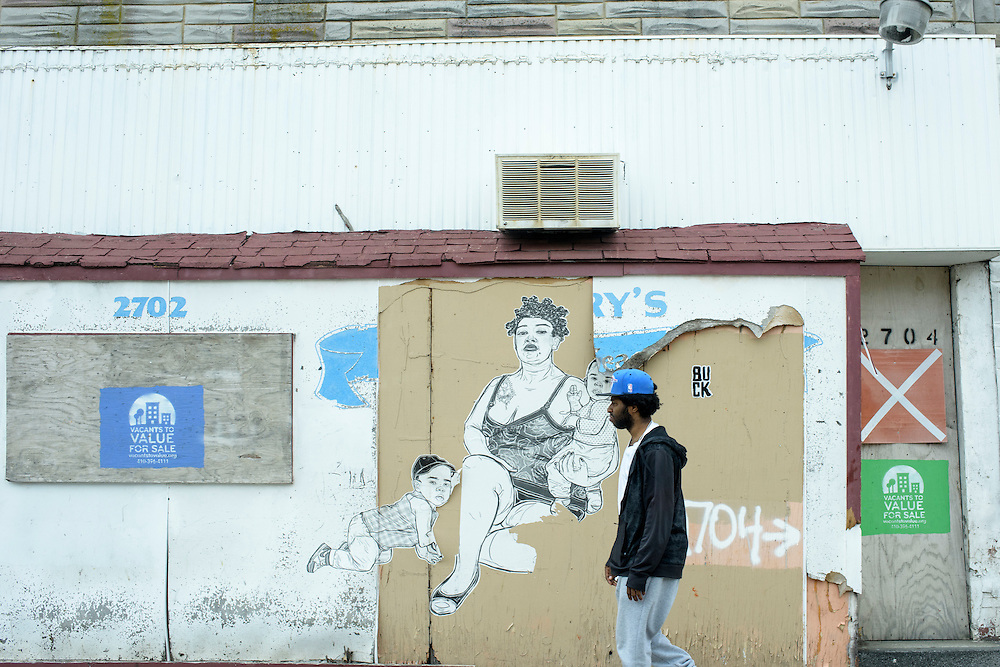 Baltimore, Maryland - April 30, 2015: A man walks past a mural in the Sandtown neighborhood of Baltimore Thursday April 30, 2015.<br /> <br /> The poor, predominately black area of Baltimore known as Sandtown is where the most violent riots occurred the week Freddie Gray was laid to rest. Tensions between the are's residents and police have been bubbling long before Freddie Gray died while in police custody. <br /> <br /> CREDIT: Matt Roth for The Globe and Mail