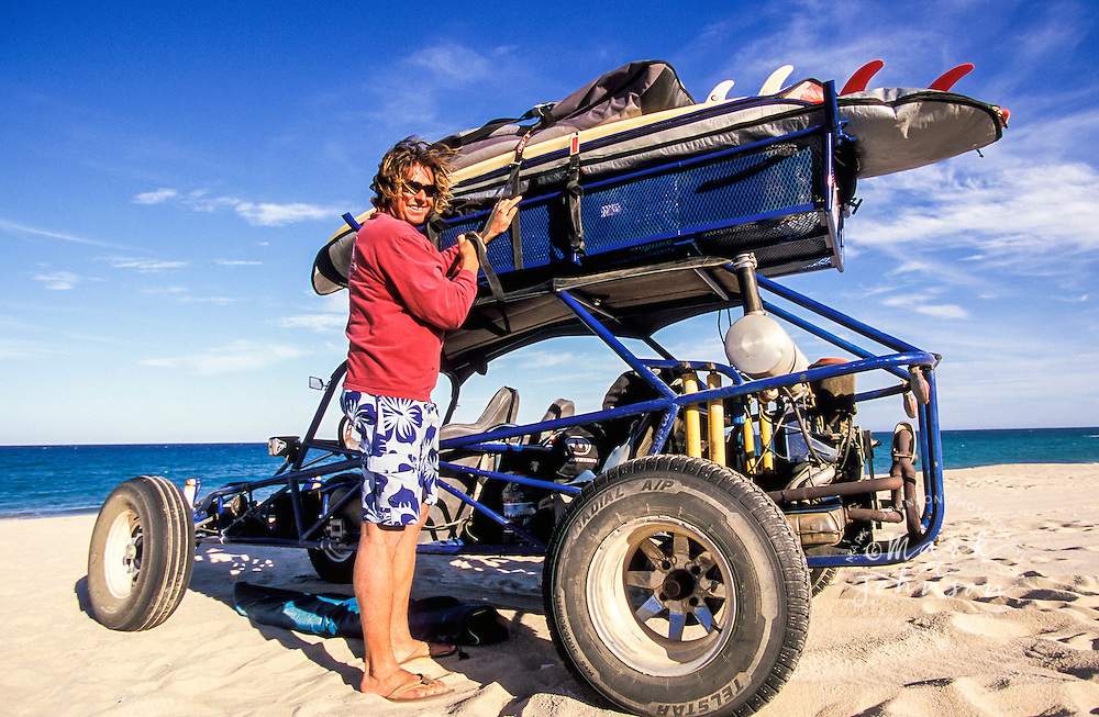 Surfer strapping down boards on dune buggy, Baja California, Mexico
