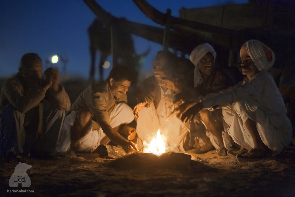 A group of men are gathered around a camp fire in the Thar desert, Rajasthan, India.