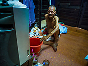 04 JULY 2017 - BANGKOK, THAILAND:  A 78 year old man who has lived in Pom Mahakan his entire life watches TV in his new home. His family was able to prove their familial roots in the community and the city allowed them to remain. The final evictions of the remaining families in Pom Mahakan, a slum community in a 19th century fort in Bangkok, have started. An ad hoc group of housing advocates, historic preservationists and academics have asked the city to allow the remaining residents to stay and city officials have said they might allow people who can prove that their families have lived in the fort since before the 1950s, when the city got title to the land from the Thai military, will be able to stay.   PHOTO BY JACK KURTZ