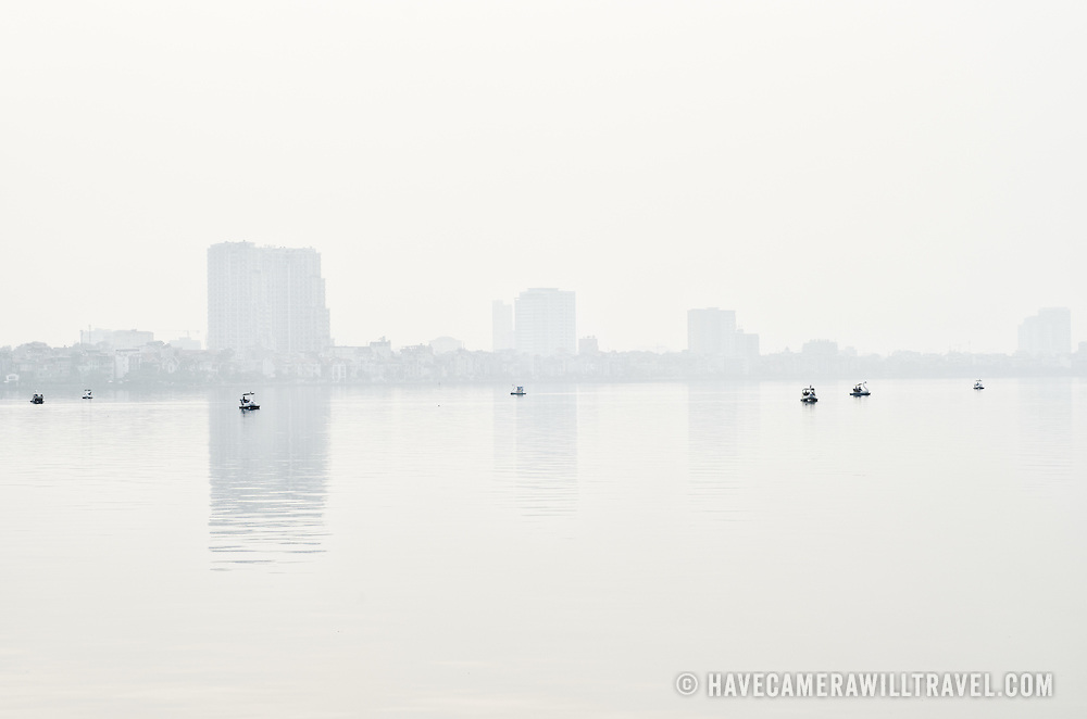 On a hazy day, small paddle boats shaped as swans dot the calm waters of West Lake (Ho Tay) in Hanoi, Vietnam.