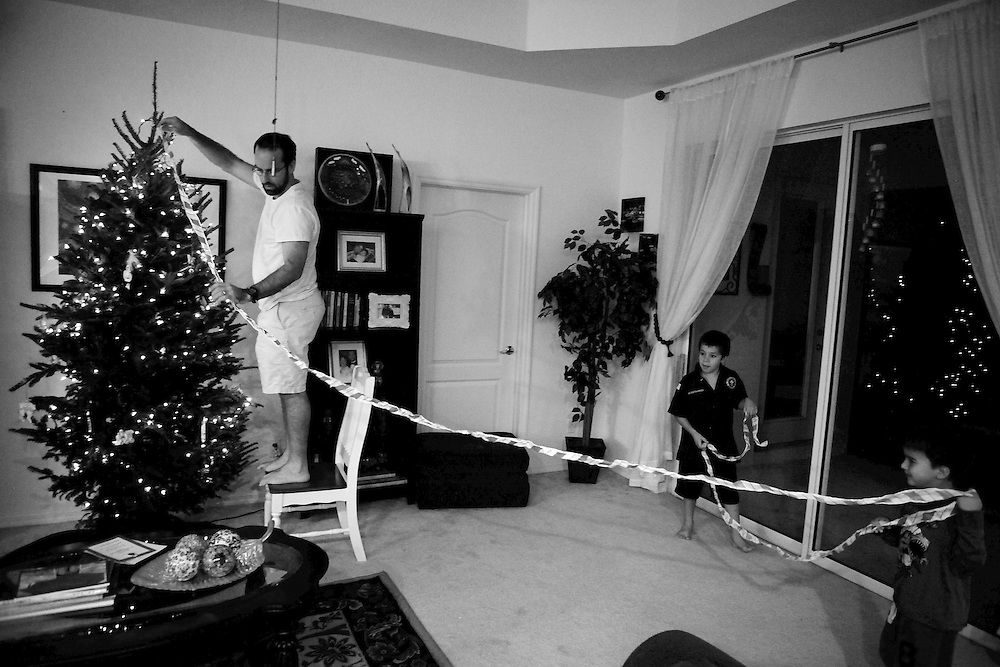 "David Kennison, left, attempts to decorate the Christmas tree with the help of his son, James, far right, and Manuelo, James' cousin, center. It was the first Christmas since David's daughter, Ellie, died. Luisa, David's wife, couldn't bring herself to take part in any of the festivities. ""It's very stressful to me,"" Luisa said. ""There's no joy. How do we even do Christmas cards? We can't put a picture together. Not all of us are here."""