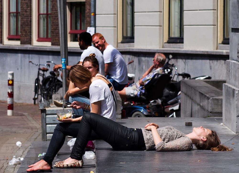 Bij het gemeentehuis in Utrecht ligt een meisje te zonnen op de eerste echte zomerse dag van 2013.<br /> <br /> In front of the city hall in Utrecht a girl is sunbathing on the first real summers day of 2013.