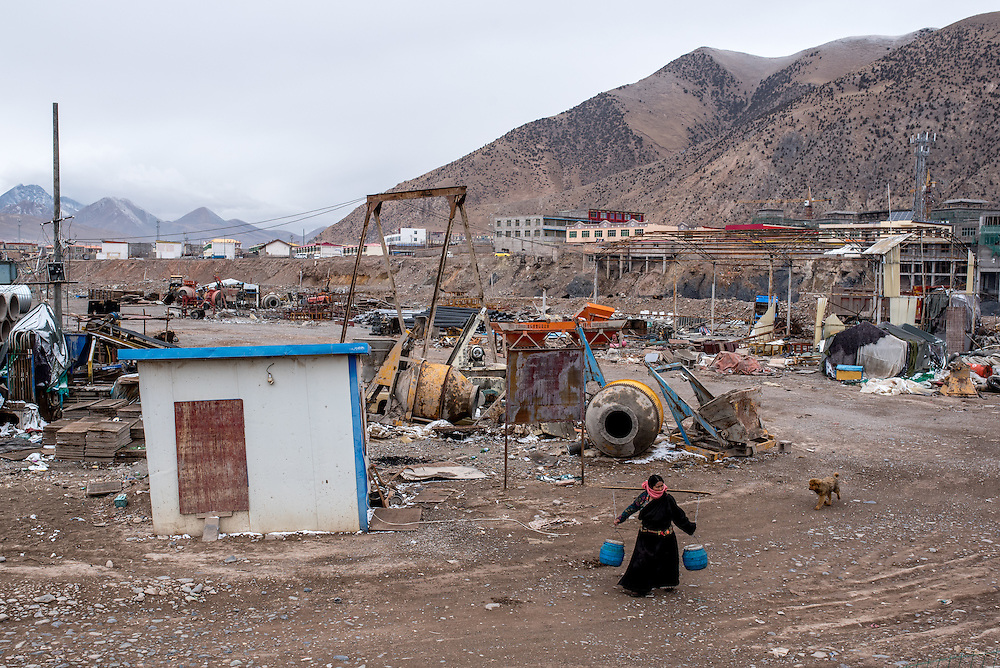 A woman walks through an industrial construction yard along the Mekong river in Zado, Tibet (Qinghai, China).