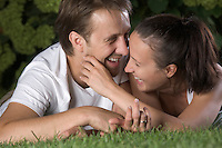 Young couple lie laughing in grass