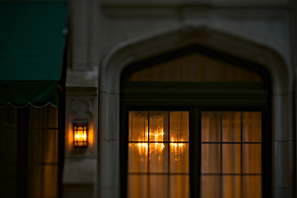 Exterior of fancy stone building with chandelier shining through sheer curtain, New York, NY