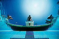 Underwater view of swimmers on diving boards