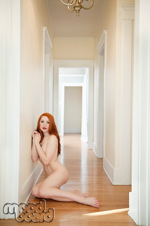 Young redheaded woman sitting on wood floor at home