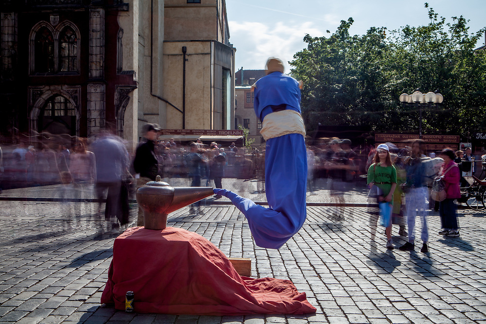 "A street perfomer who refers to  ""Aladdin and the magic lamp"" perfoming in-front of a crowd at Old Town Square."