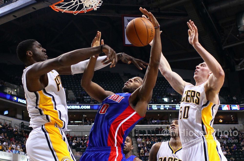 Feb. 23, 2011; Indianapolis, IN, USA; Detroit Pistons power forward Greg Monroe (10) has his shot broken up by Indiana Pacers center Roy Hibbert (55) and Indiana Pacers forward Tyler Hansbrough (50) at Conseco Fieldhouse. Indiana defeated Detroit 102-101. Mandatory credit: Michael Hickey-US PRESSWIRE
