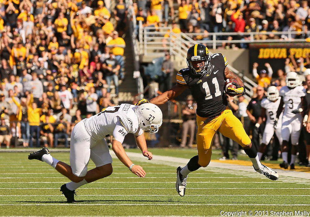 September 21 2013: Iowa Hawkeyes wide receiver Kevonte Martin-Manley (11) tries to hold of Western Michigan Broncos punter J. Schroeder (37) as he returns a punt during the first quarter of the NCAA football game between the Western Michigan Broncos and the Iowa Hawkeyes at Kinnick Stadium in Iowa City, Iowa on September 21, 2013. Iowa defeated Western Michigan 59-3.