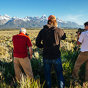 Teten Science Schools tour participants watch a herd of elk forage in the early morning hours. (Matthew Bart, Sean Baker, Dawson-guide) Tetons in the background.