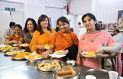Image ©Licensed to i-Images Picture Agency. 07/03/2015. London, United Kingdom. Ravi Bhanot and family, Conservative Party supporters in Ilford. Ravi's friends and family pick up food in a gathering at a local Hindu Temple. Ilford. Picture by Daniel Leal-Olivas / i-Images