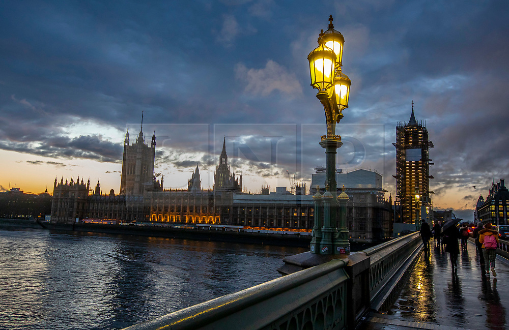 © Licensed to London News Pictures. 09/01/2020. London, UK. After the rain orange clouds over the river Thames and Parliament at sunset. Photo credit: Alex Lentati/LNP