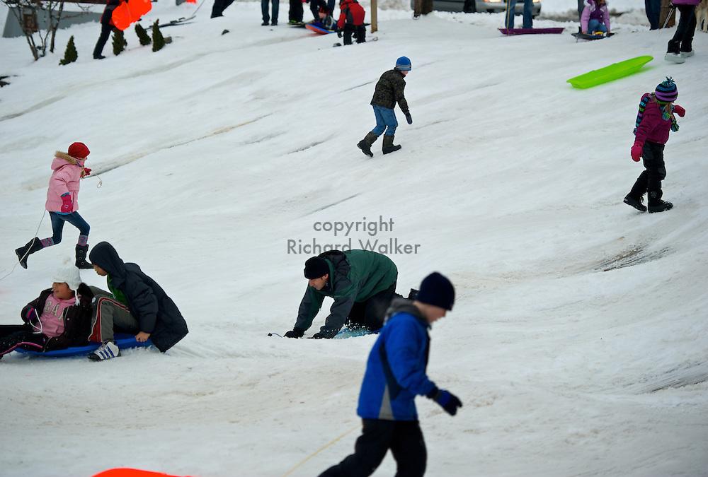 2010 December 23 - People enjoy sledding at Front Street Park at Christmas in Leavenworth, WA, USA. CREDIT: Richard Walker