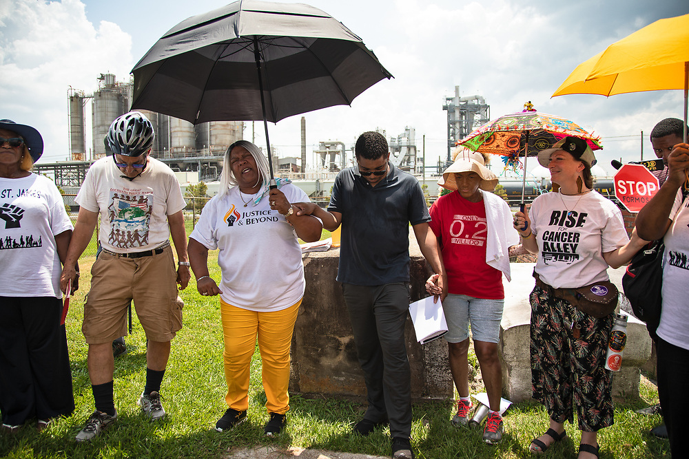 """Prayer held by members of CADA and supporters at the Reveille Town Cemetery in Plaquemine, Louisiana on the fourth day of the Coalition Against Death Alley's 5 day march. The Coalition Against Death Alley (CADA), is a group of Louisiana-based residents and members of various local and state organizations, is calling for a stop to the construction of new petrochemical plants and the passing of stricter regulations on existing industry in the area that include the groups RISE St. James, Justice and Beyond, the Louisiana Bucket Brigade, 350 New Orleans, and the Concerned Citizens of St. John.  Louisiana's Cancer Alley, an 80-mile stretch along the Mississippi River, is also known as the """"Petrochemical Corridor,"""" where there are over 100 petrochemical plants and refineries. The cemetery is located within the fenceline of Westlake Chemical plant that controls acess to it."""