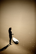 Surfer Standing On Beach With Surfboard