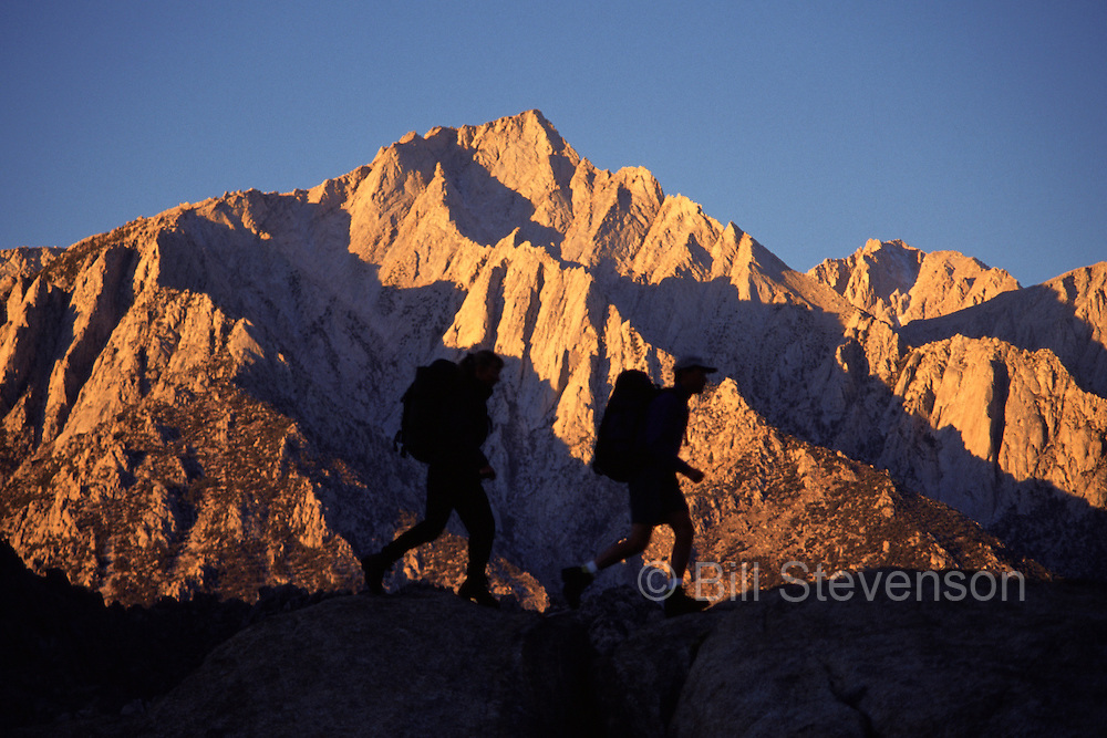A photo of two silhouetted people hiking in front of Lone Pine Peak at sunrise in the Sierra Mountains of California,
