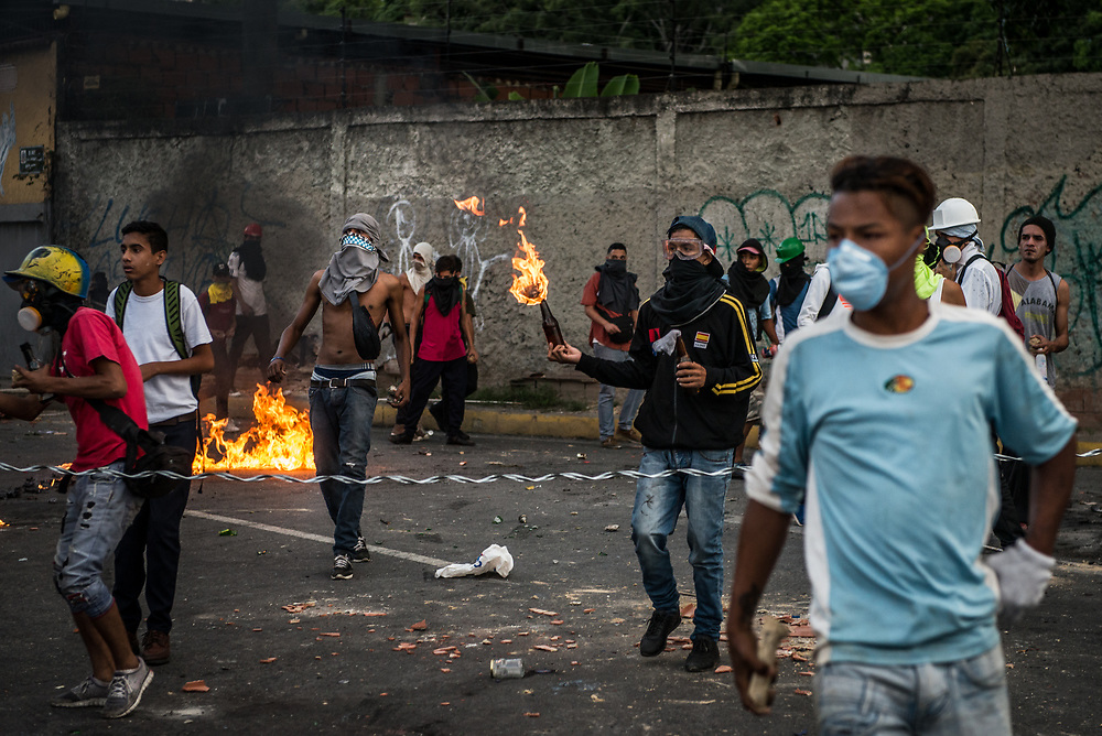 CARACAS, VENEZUELA - JUNE 2, 2017:  Anti-government protesters hurl stones and molotov cocktails during clashes with members of the National Police, who responded by heavily tear gassing and firing rubber bullets and buckshot at them. The streets of Caracas and other cities across Venezuela have been filled with tens of thousands of demonstrators for nearly 100 days of massive protests, held since April 1st. Protesters are enraged at the government for becoming an increasingly repressive, authoritarian regime that has delayed elections, used armed government loyalist to threaten dissidents, called for the Constitution to be re-written to favor them, jailed and tortured protesters and members of the political opposition, and whose corruption and failed economic policy has caused the current economic crisis that has led to widespread food and medicine shortages across the country.  Independent local media report nearly 100 people have been killed during protests and protest-related riots and looting.  The government currently only officially reports 75 deaths.  Over 2,000 people have been injured, and over 3,000 protesters have been detained by authorities.  PHOTO: Meridith Kohut