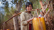 Country girl carrying water in plastic containers (Myanmar)