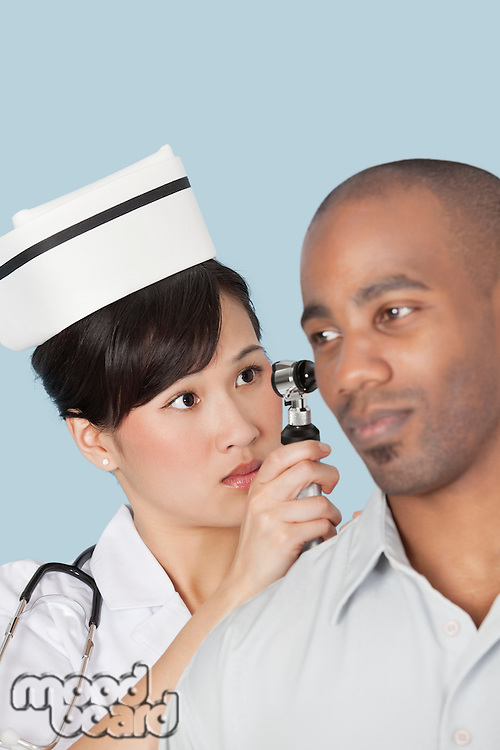 Nurse examining male patient's ear over light blue background