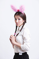 Frightened young woman with bunny ears against white background