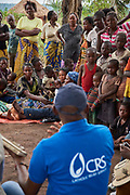 CRS staff speak to a gathering of villagers including the chief, men, women and children to explain in detail the ARCC III project involving emergency cash transfers to beneficiaries as part of a program being implemented in the village of Lumbambala, Province of Lomami, Democratic Republic of Congo on September 16, 2017. Many of the villagers fled their homes into the bush in March/April 2017 as the Kamwina Nsapu militia battled with security forces in the villages. When CRS visited the village in July, 2017, many of the villagers had still not returned. When they eventually returned, many found their homes had been burnt down. Many of the villagers are living in makeshift shelters while they attempt to rebuild them. To assist these returnees, CRS teams interview each household to determine if it will receive assistance. The ARCC III project has been implemented in four zones, with each household receiving between $5-$25 depending on their vulnerability. The program also involves an awareness component on how to potentially spend the the money with focus on nutrition, education and healthcare. As part of the monitoring and evaluation component, CRS teams return 1 month later to the zone and interview beneficiaries to learn how they have spent the money.