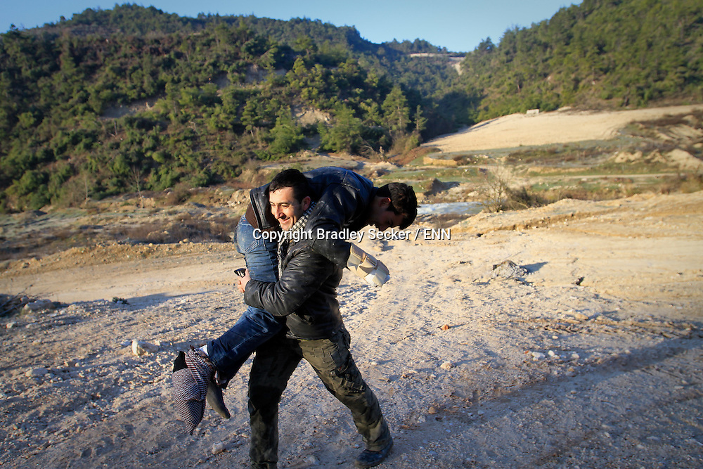 A Free Syrian Army soldier carries a wounded soldier to safety after crossing a river near Al Janoudiyah, Syria.