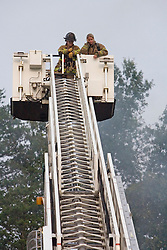 Two female fire fighters on top of a bucket ladder while fighting a house fire.