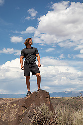 good looking male hiker on top of a mountain