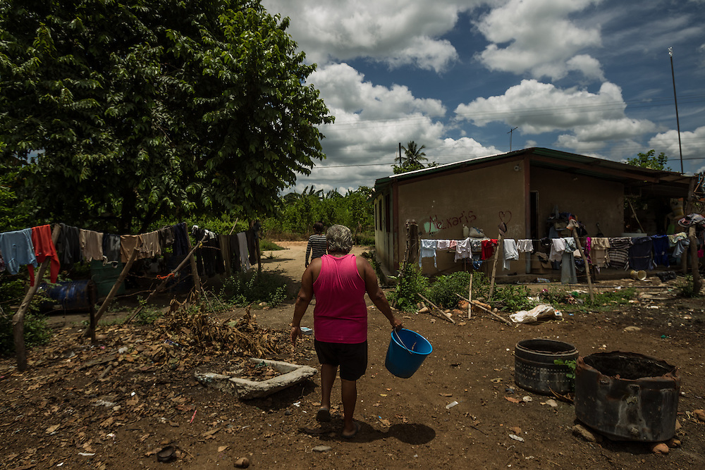 """BARALT MUNICIPALITY, VENEZUELA - AUGUST 28, 2014: Dolores de Welfer Delgado, 56,  a seamstress struggling to make ends meet, returns to her home after putting laundry out to dry on a barbed wire fence. She lives with her family close to oil wells in the Baralt municipality of Zulia state but say they've never reaped any benefits from the oil found so close to their home. """"Look at the riches of Venezuela,"""" said Ramón Materán, 64, a laborer. """"For all of Venezuela's riches things are pretty neglected here."""" PHOTO: Meridith Kohut for The New York Times"""