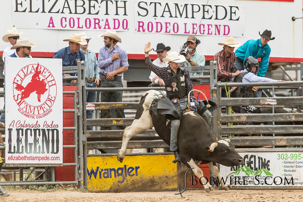 Bull rider Brett Custer rides Summit Pro Rodeo's Jungle Ape during the third performance of the Elizabeth Stampede on Sunday, June 3, 2018.