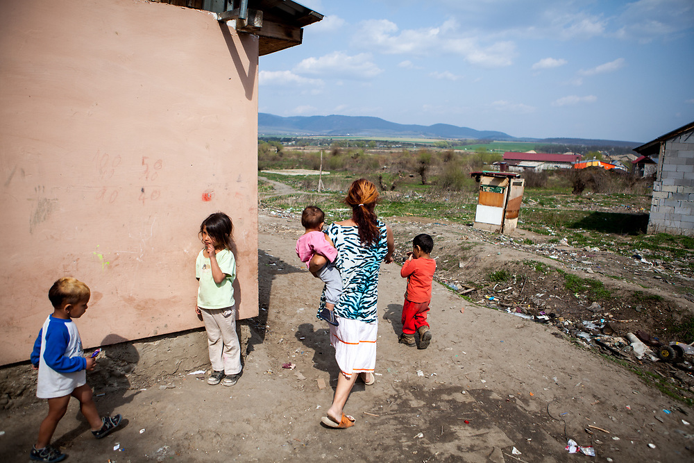 A mother walking with her children at the Roma settlement in Ostrovany.