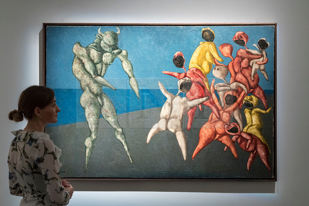 """© Licensed to London News Pictures. 20/04/2018. LONDON, UK. A staff member views """"Il Minotauro Fa Paura Alla Gente Per Bene (The Minotaour Scares the Good People"""" by Bahman Mohasses (Est. GBP280-350k) at a preview of works in Sotheby's 20th Century Middle East, Orientalist and Islamic upcoming art sales in New Bond Street.  The works will be sold at auction in the last week of April.    Photo credit: Stephen Chung/LNP"""