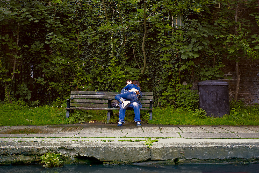 Pair of lovers snuggle on a bench alongside the Regent's Canal.  Leafy background; canal edge and a sliver of water in foreground.  They are alone in their absorption with each other and nobody else nearby.  Both wear denim jeans.  He holds her curled up in his lap.