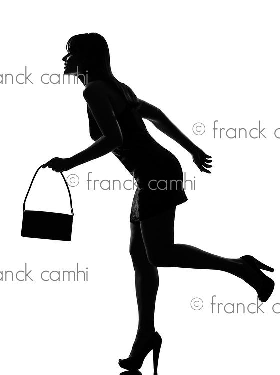 stylish silhouette caucasian beautiful woman running holding purse full length on studio isolated white background