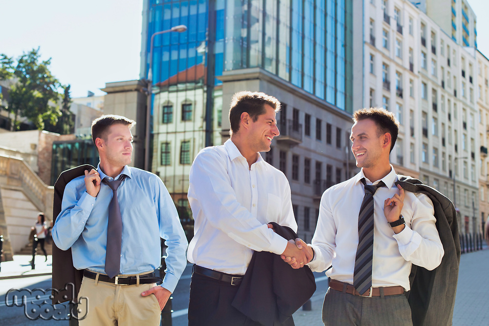 Portrait of handsome mature businessman shaking hands with colleague after meeting against office building