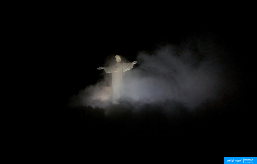 The iconic Cristo Redentor, Christ the Redeemer statue  appears out of the clouds while lit up at night time atop the mountain Corcovado. The Christ statue was voted one of the seven wonders of the modern world in 2007. It was designed by Brazilian Heitor de Silva Costa and was inaugurated in 1931 having taken years to assemble. Rio de Janeiro, Brazil. 24th July 2010. Photo Tim Clayton...