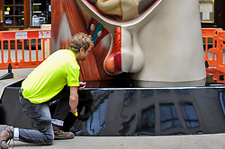 """© Licensed to London News Pictures. 24/06/2017. London, UK. A workman polishes the plinth of a 21 feet tall, 2.5 tonne bronze sculpture called """"Temple"""" by Damien Hirst that has been unveiled near the Lloyds Building in the City of London.  The artwork will be on display as part of """"Sculpture in the City"""", a festival of sculpture in the City of London showing works by leading artists. Photo credit : Stephen Chung/LNP"""