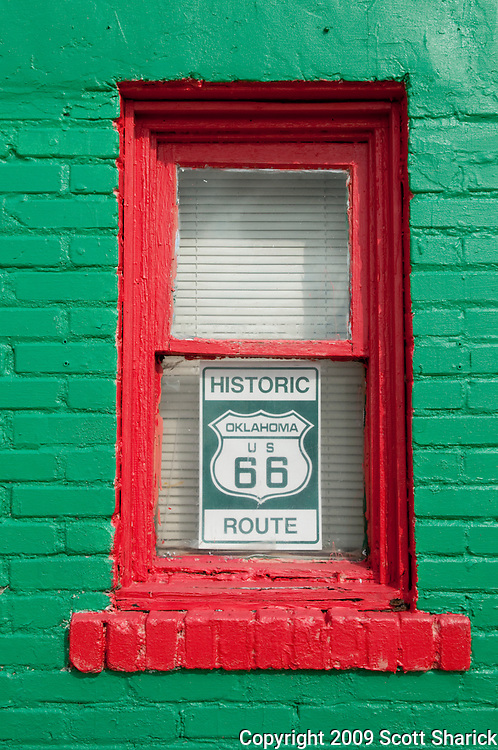 A Historic Oklahoma Route 66 sign in a red window in a green brick building. Missoula Photographer