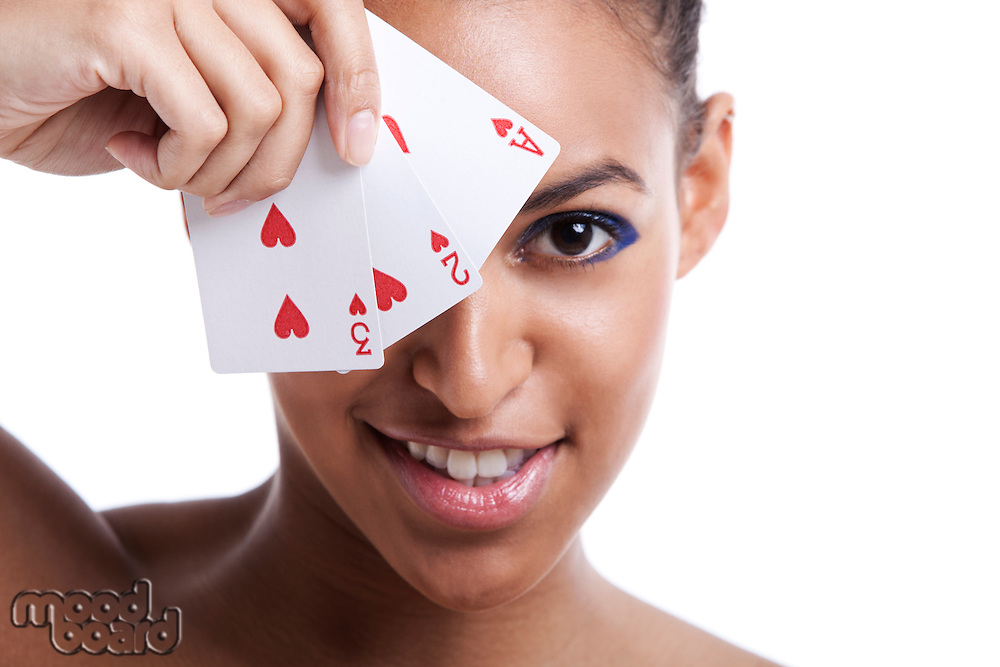 Portrait of young Mixed Race woman with playing cards biting her lip against white background