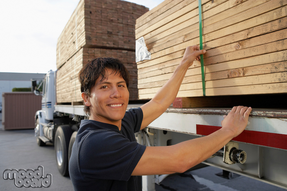 Young Man Checking Load on Truck Trailer