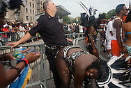 The 44th Annual West Indian Labor Day Parade , took place today on Eastern Parkway in Brooklyn. It is considered to be New York City's largest with 3.5 million particapants. A  costumed woman,  danced on a policer officer guarding a barricade along the parade route.
