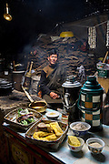 Karsal, a nomadic yak herder, with his typical day's worth of food inside the family's yak-wool tent in the Tibetan Plateau. (From the the book What I Eat: Around the World in 80 Diets.) The caloric value of his day's worth of food in June was 5,600 kcals. He is 30 years of age; 5 feet, 6 inches tall; and 135 pounds. A pile of yak dung, used for fuel, looms in the background. MODEL RELEASED.