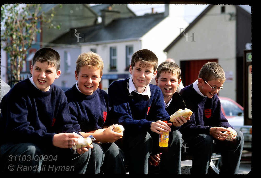 Schoolboys sit on back of park bench eating their lunch on a September day in Castletownbere; Beara Peninsula, Ireland.