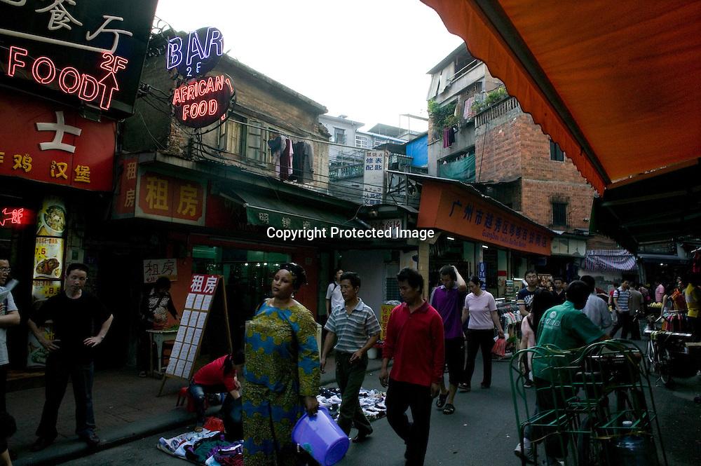 GUANGZHOU, 3. Mai , 2010:.eine Afrikanerin geht auf einer Marktstrasse in der Naehe des Tianxiu Kaufhauses in Guangzhou...