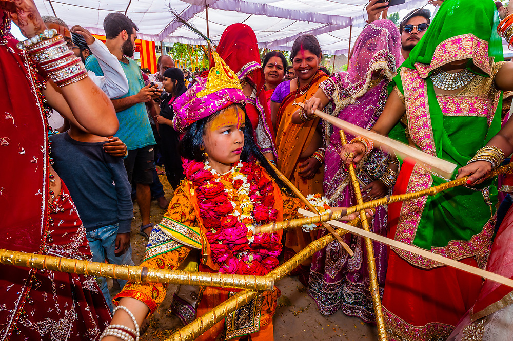 Girl dressed as Radha (Hindu goddess; lover and companion of Hindu God, Krishna) plays Lathmar Holi with sticks, Chhadi Mar Holi (local Holi (festival of colors); village of Gokul, near Mathura, Uttar Pradesh, India.